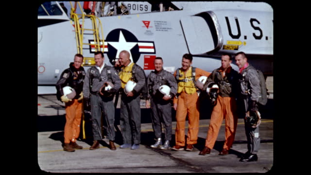 Mercury 7 astronauts wearing flight suits and posing for photographs in front of Convair 106B aircraft / They are left to right M Scott Carpenter L...