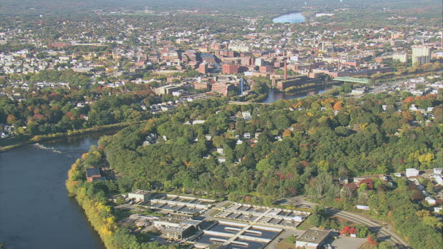 AERIAL Merrimack River with bridges, and old mills and factories clustered along the riverbank / Lowell, Massachusetts, United States