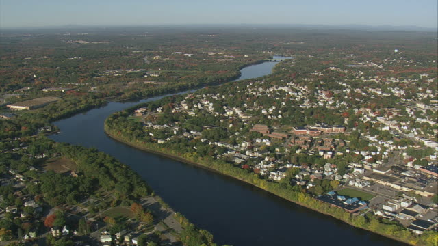 AERIAL Merrimack River with residential and commercial districts beyond / Lowell, Massachusetts, United States