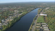 AERIAL Merrimack River with the city lining both riverbanks and bridges crossing / Lowell, Massachusetts, United States