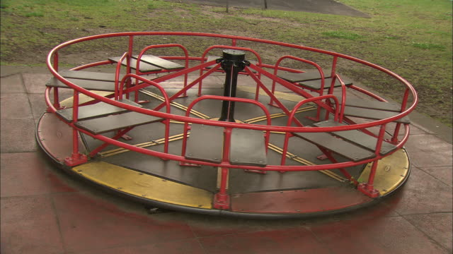 A merry-go-round slowly turns in the middle of a park.