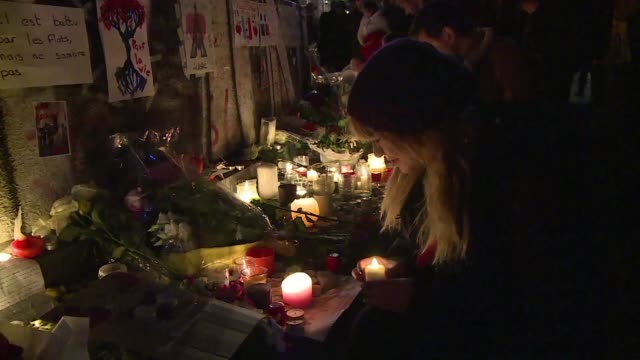 Messages flowers candles lit up memorials and vigils across Paris on Saturday night as the city grapples with the deadliest attacks in Frances history