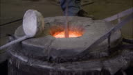 A metal caster lifts a ladle from molten metal at a foundry.