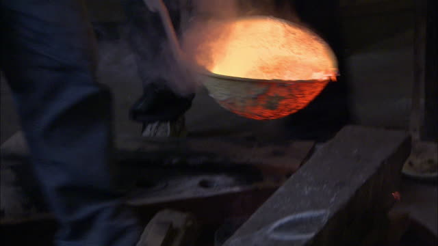 A metal caster uses a ladle to pour molten metal into a furnace at a foundry.