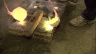 Metal casters pour molten metal from ladles into molds at a foundry.