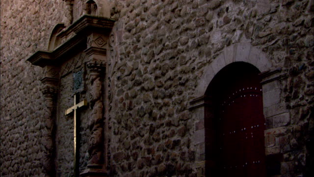 A metal cross hangs inside an ornately carved wood frame on the side of a cobblestone building. Available in HD.
