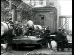1914 MONTAGE B/W WS PAN Metal factory workers hoisting cylinders onto cart on street outside factory/ Russia