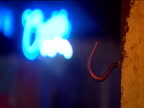 Metal hook in wooden post with out-of-focus neon sign in background. Bar game in which attempts are made to throw metal ring on string over a hook successful on third attempt