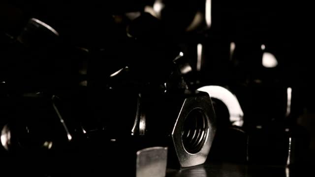 Metal nuts turn around in dark scene.