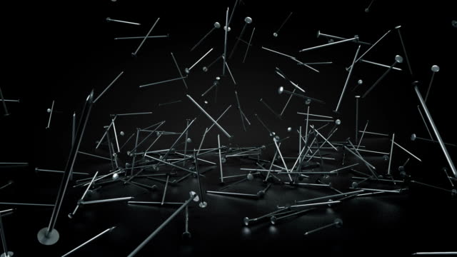 Metal pins fall and hit the floor in a black room