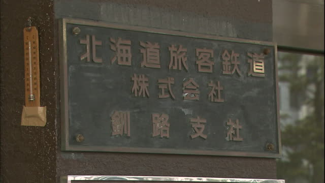 A metal plaque with Kanji characters and a thermometer are on a pillar near the entrance of the Kushiro Railway Station.