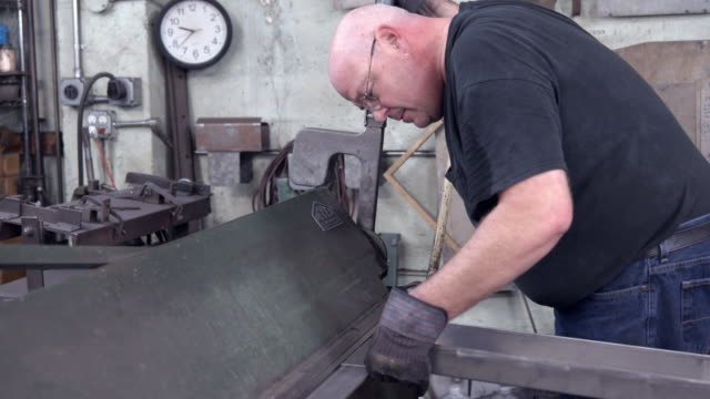 metal worker clamps shaped piece of metal into vintage bending press and pulls large lever to bend metal into exact right angle / Redlands, California, USA