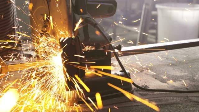 Metallarbeiter Schleifen Eisen mit elektrischem sah während der Arbeit in einer Werkstatt.