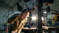 Metal worker using a drill press in a workshop