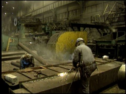 Metal workers work with heavy machinery