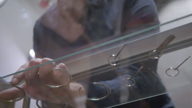 CU. Meticulous shop owner straightens rings and bracelets on glass display case.