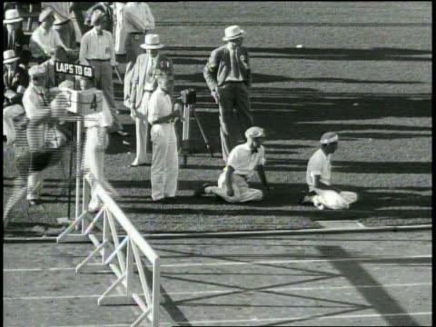 3000 metres steeplechase / wide pan shot [starting with audience and man in white sailor's hat descending the bleachers in foreground] of runners...