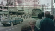 1976 MONTAGE Metro bus picking up commuters, and workers managing a computerized traffic flow monitoring system / Leeds, England, United Kingdom