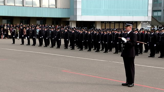 Hendon Police College passing out parade / Boris Johnson interview Various of police recruits standing at parade as military music and National...
