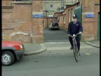 Metropolitan police officer leaves local police station on bicycle London; 1994
