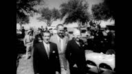 / Mexican President Adolfo Lopez Mateos visits Senator Lyndon Johnson at his ranch in Texas / exits car and shakes hands with people in sombreros /...