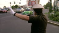 A Mexico City police officer signals traffic to move quickly through an intersection.