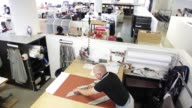 Michael Hill managing director of Drake's selects a roll of fabric at the tailors factory outlet store in London UK on Friday June 26 2015 Shots A...