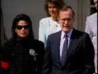 Michael Jackson sunglasses President George HW Bush standing together at White House Rose Garden for press Bush welcoming Jackson shaking hands...