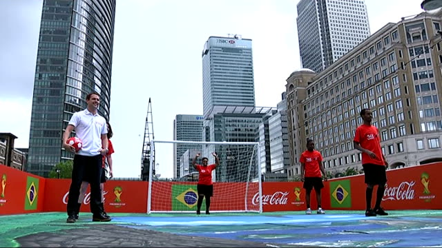 Michael Owen unveils street artwork in Canary Wharf ahead of World Cup ENGLAND London EXT Michael Owen posing for photocall with football / Owen and...