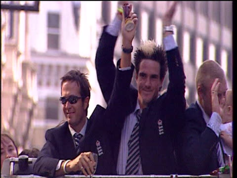 Michael Vaughan holds Ashes trophy aloft with fellow England cricket team members Kevin Pieterson and Andrew Flintoff standing beside him on open top...