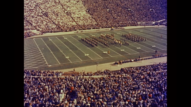 WS HA Michigan Stadium, crowd watches marching band form letters MICH on the field / Ann Arbor, Michigan, United States