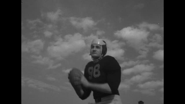 VS Michigan Wolverine football player Tom Harmon posing in football action shots / Note exact month/day not known