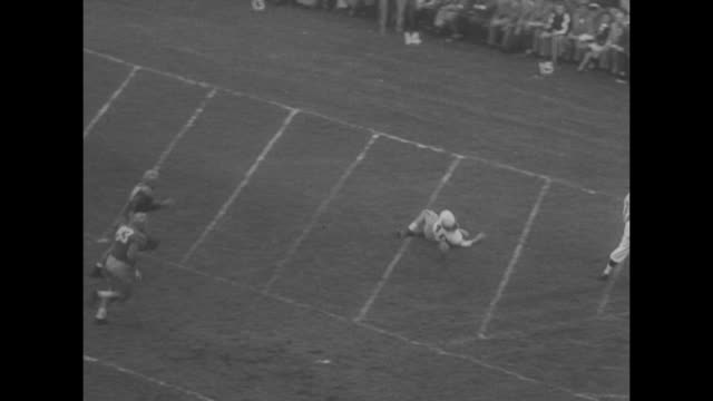 Michigan Wolverines player Ted Kress runs many yards on field dodging multiple Tulane Green Wave players and crosses end zone for touchdown / crowds...