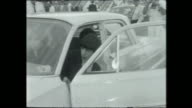Mick Jagger and other Rolling Stones band members including Bill Wyman hustle into cars on tarmac and driven away / Close up of bent over cyclone...