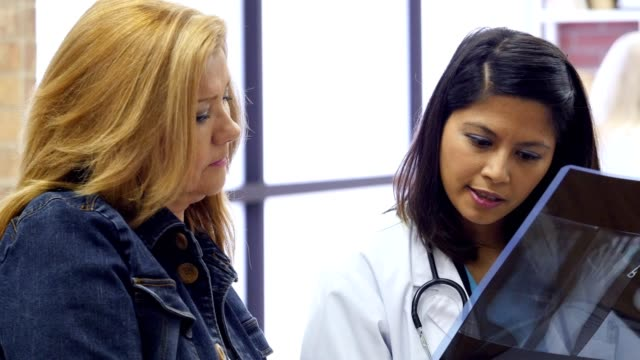 Mid adult Asian female doctor consults with a colleague