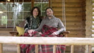Mid adult couple holding hands while sitting on a swing bed