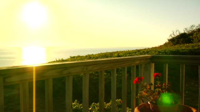 WS, PAN, Mid adult couple relaxing on cottage porch at sunset, North Truro, Massachusetts, USA