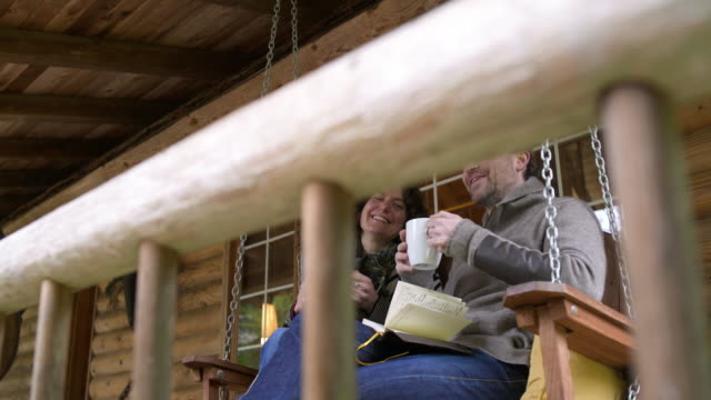 Mid adult couple talking while sitting on a swing bed