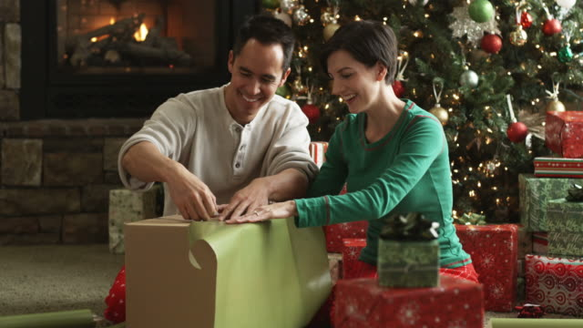 mid adult couple wrapping Christmas presents