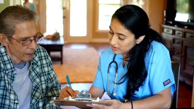 Mid adult Hispanic home healthcare nurse reviews information with senior patient