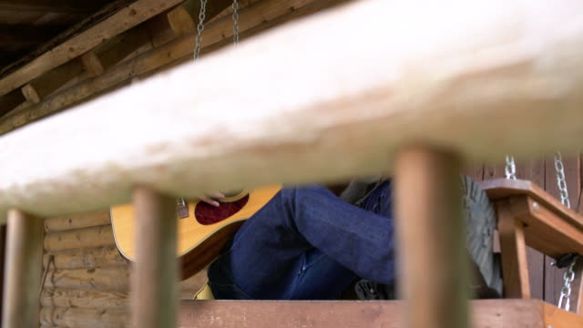 Mid adult man playing guitar while sitting on a swing bed
