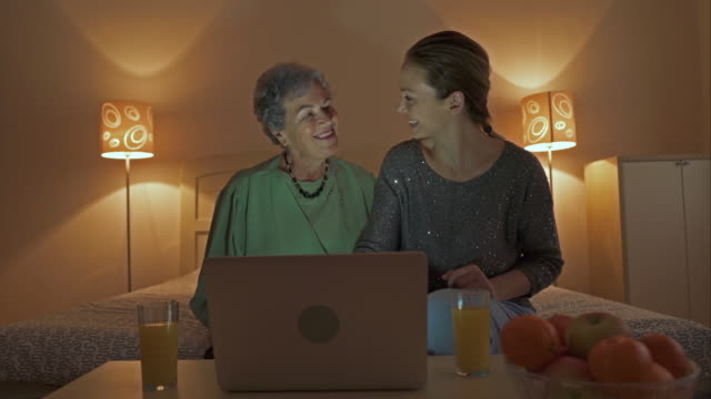 Mid adult woman and her mother having video chat over laptop and waving to someone.