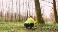 SLO MO Mid adult woman doing squats in the forest