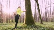 SLO MO Mitte Erwachsene Frau tun stretching Übungen in einem Wald
