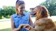 Mid adult woman enjoys playing with dog in dog park