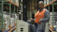 Mid adult woman standing on a forklift