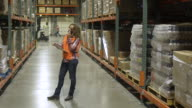 Mid adult woman using a walkie-talkie in a warehouse