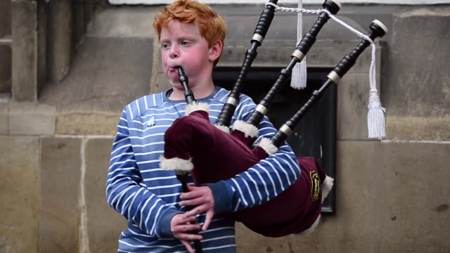 Mid Shot A Boy Is Playing Bagpipes Street entertainers perform on Edinburgh's Royal Mile during the city's Festival Fringe on August 21 2013 in...
