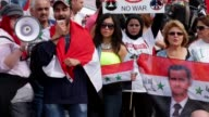 Mid Shot a demonstrators use a megaphone to shout messages to President Barack Obama