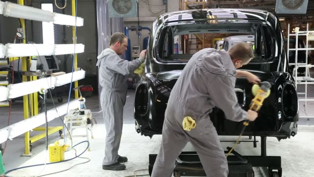 Mid Shot factory workers polishing a TX4 body Workers inside the factory of The London Taxi Company attach the body of a TX4 London Taxi to its...